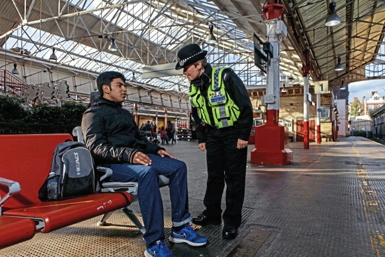BTP Officer talking to teen boy on railway platform