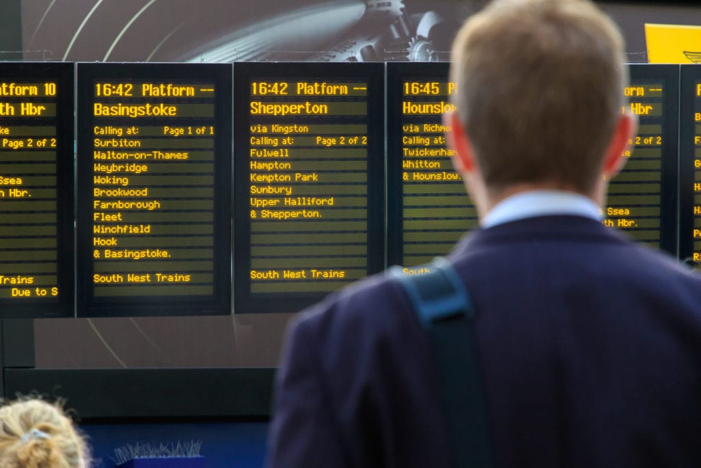 Commuter checking the digital timetables at Waterloo train station
