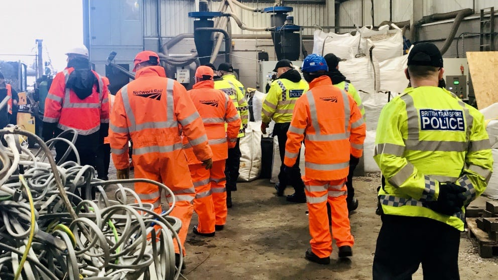 Members of Network Rail and BTP in visibility jackets stand inside a warehouse.
