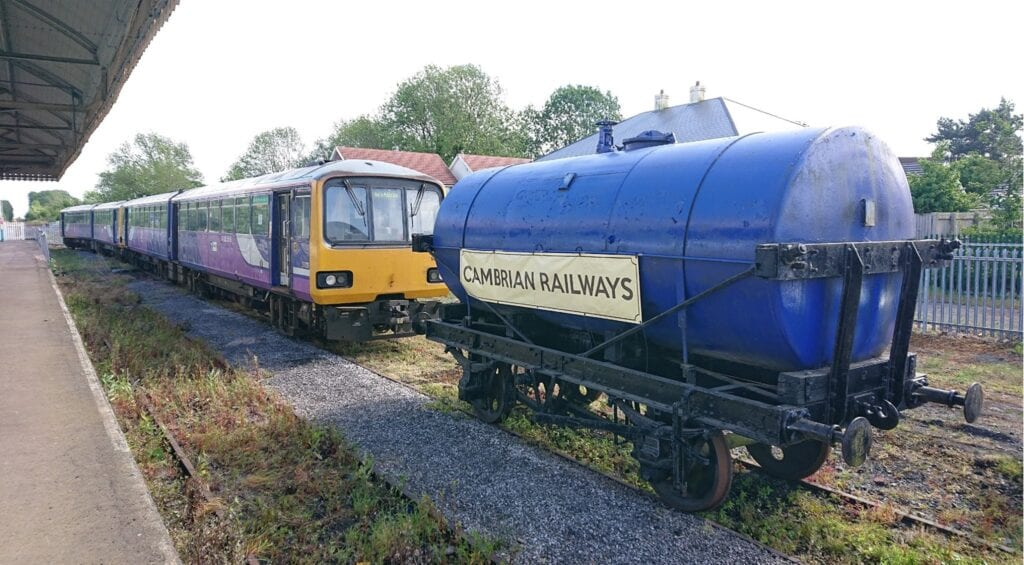 Class 144 Pacers Nos. 144006/07 are seen at their temporary new home after arrival on May 22– the CHR-owned former coal yard sidings a Gobowen. The restored tank promotes the Cambrian Heritage Railways project. PHIL BRADLEY/CHR